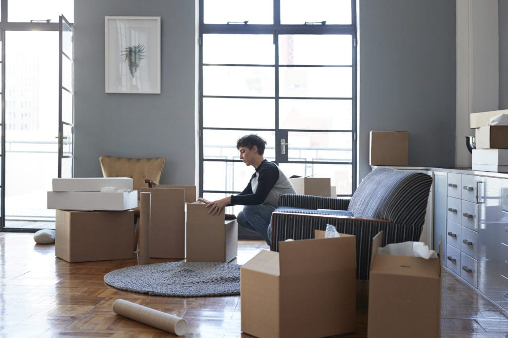 Woman packing boxes in apartment before moving