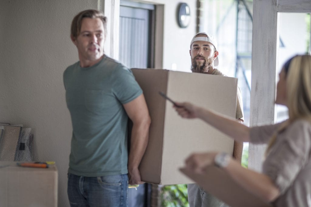 Movers carrying a cardboard box into a house