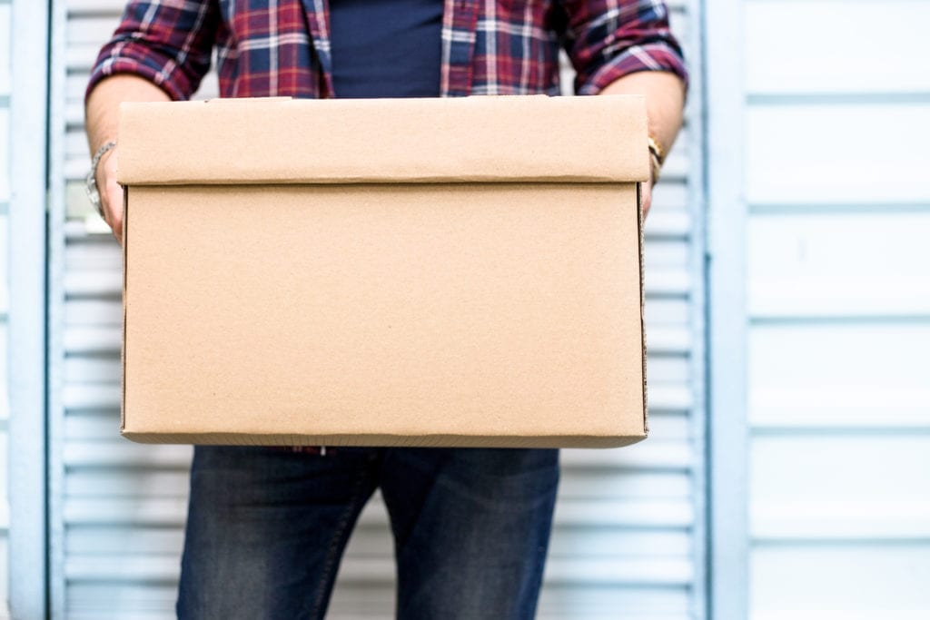 Man holding cardboard box in front of storage container