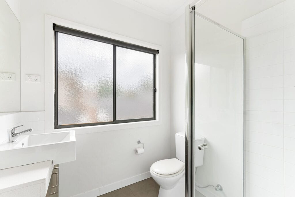 Textured windows allow for light and privacy in the bathroom.