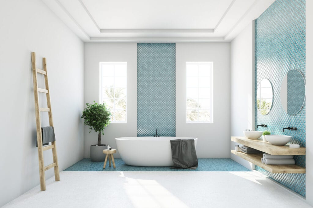 White and blue bathroom interior with a round white tub, two narrow windows, a tree in a pot and a ladder in a corner. Side view.