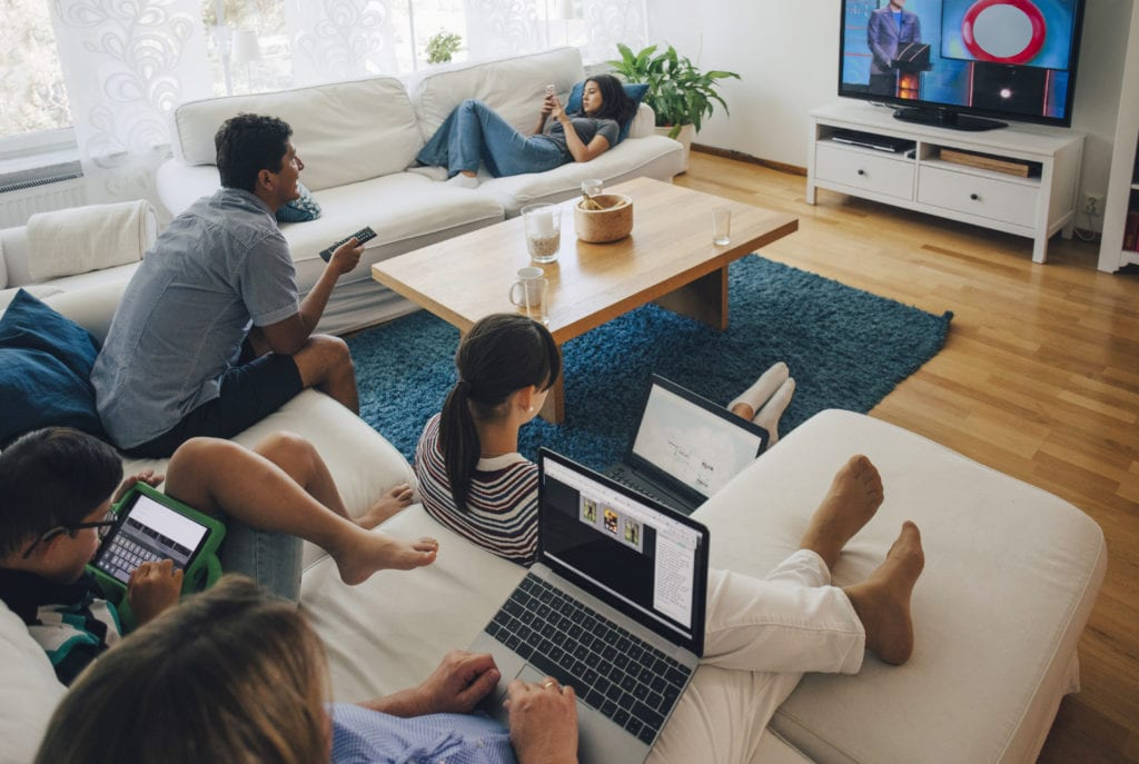 family on laptops and tablets watching tv