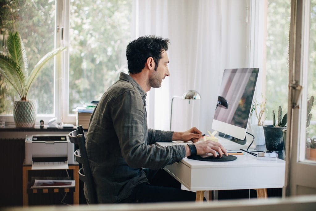 man uses desktop computer in home office