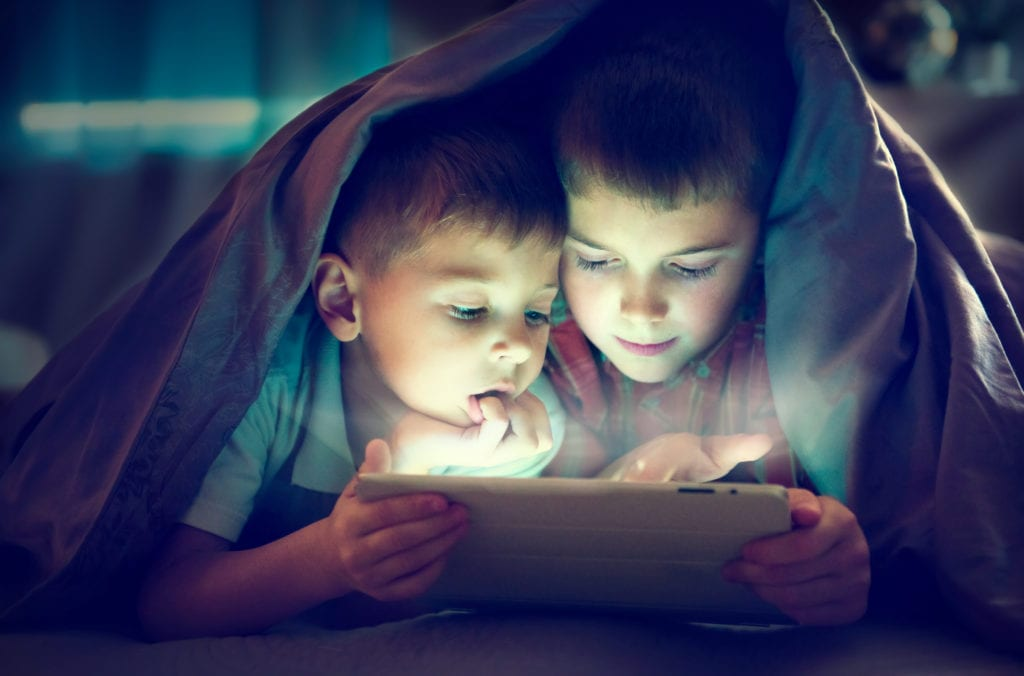Kids using tablet under a blanket