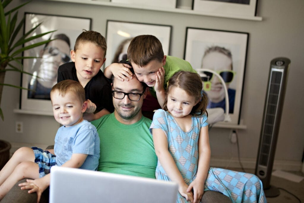 Dad and kids watching a computer