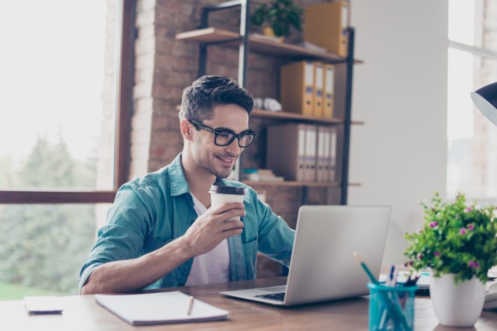 man holding coffee using laptop