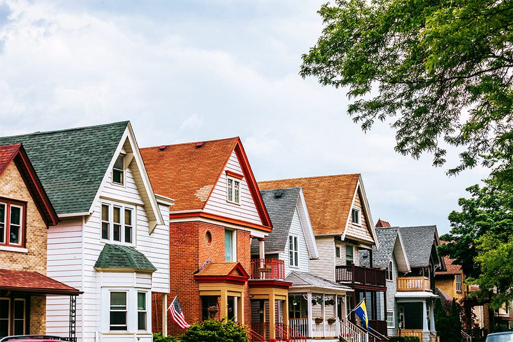 A colorful row of houses in what looks to be an appealing and safe neighborhood.
