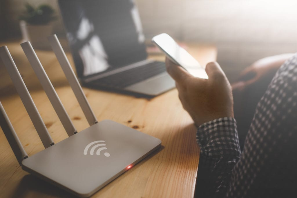 Person on phone next to internet router