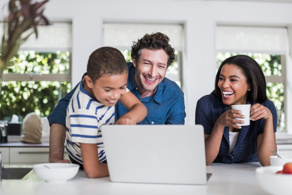 Happy boy showing something to parents on laptop in kitchen at home