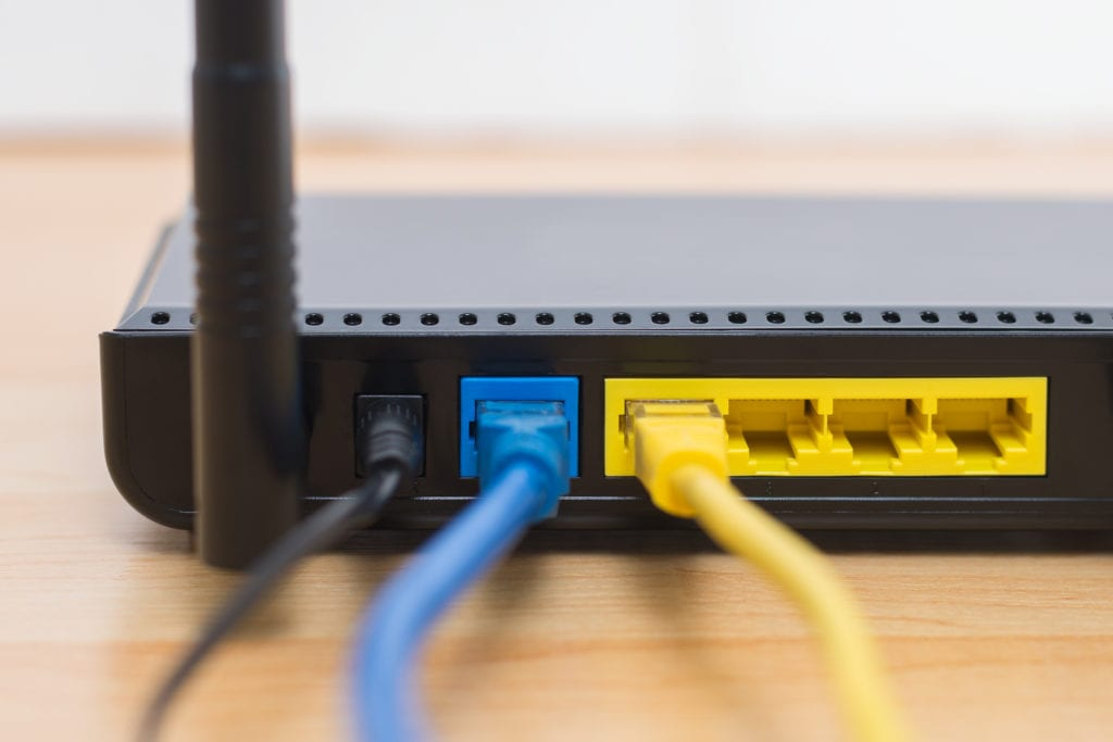 Close up of modem or router with black, blue, and yellow wires