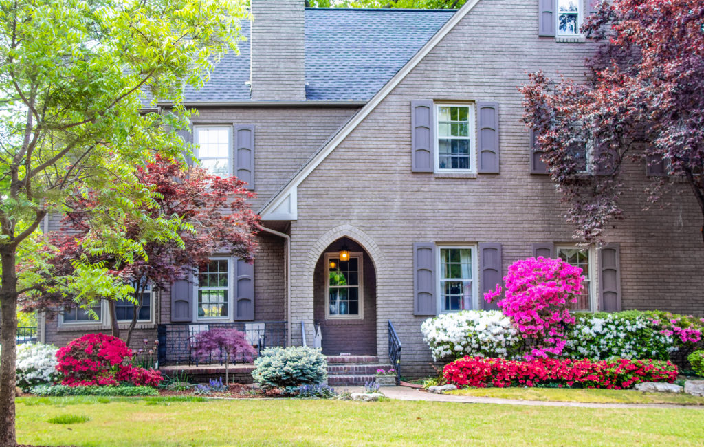Brick two story house with Japanese Maples and Azaleas in front yard landscape