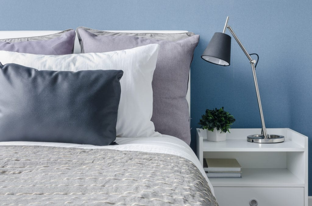 Modern bedroom with blue walls and black table lamp