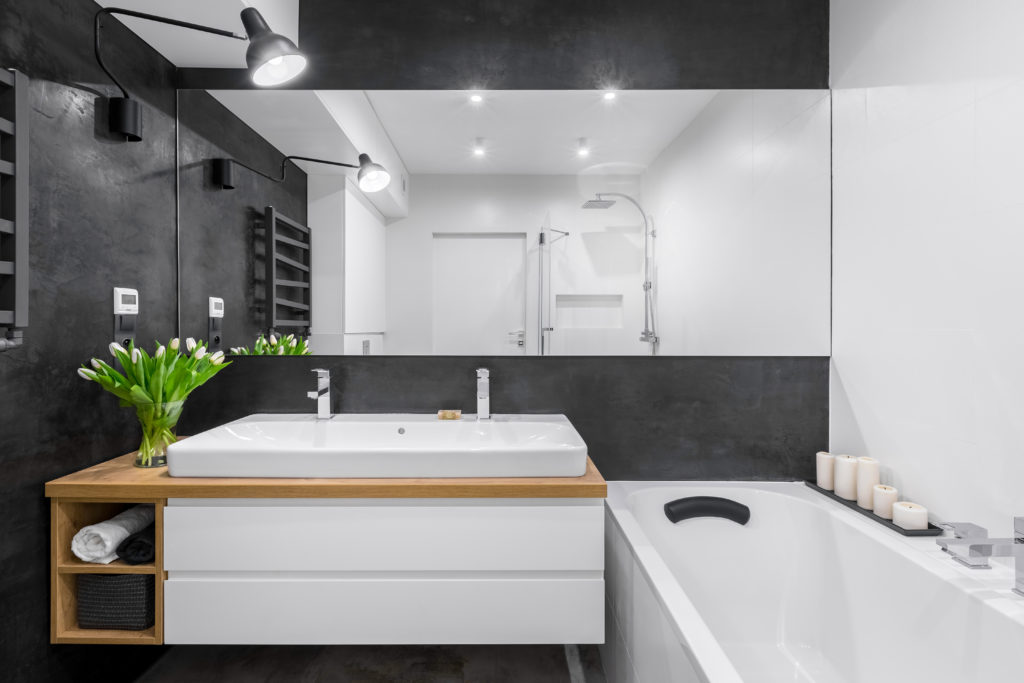 Modern bathroom interior with black wall and wide mirror
