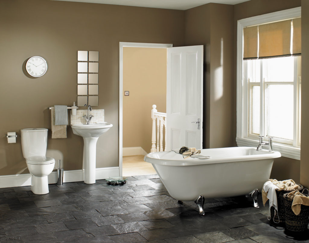 Bathroom with white tub and sink, and brown walls