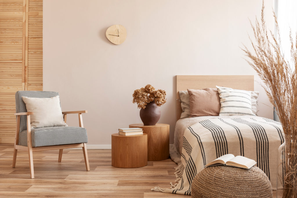 Beige room with wooden floors, wooden headboard, and stylish armchair