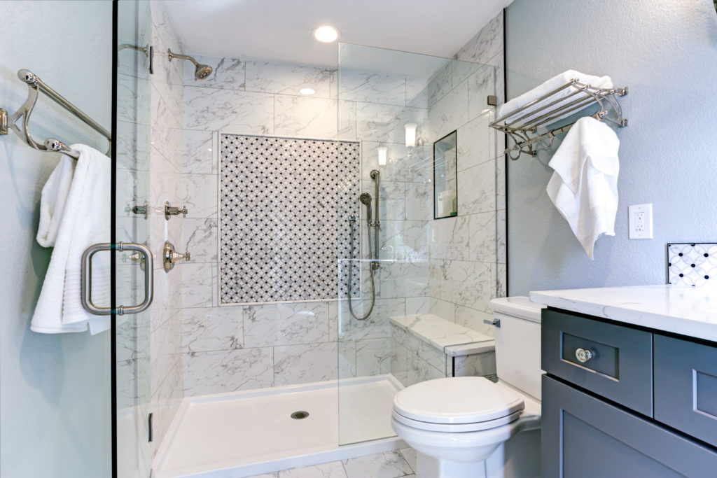 Bathroom with blue cabinets and marble shower tiles