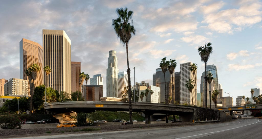 Photo of los angeles skyline with palm tree and clouds
