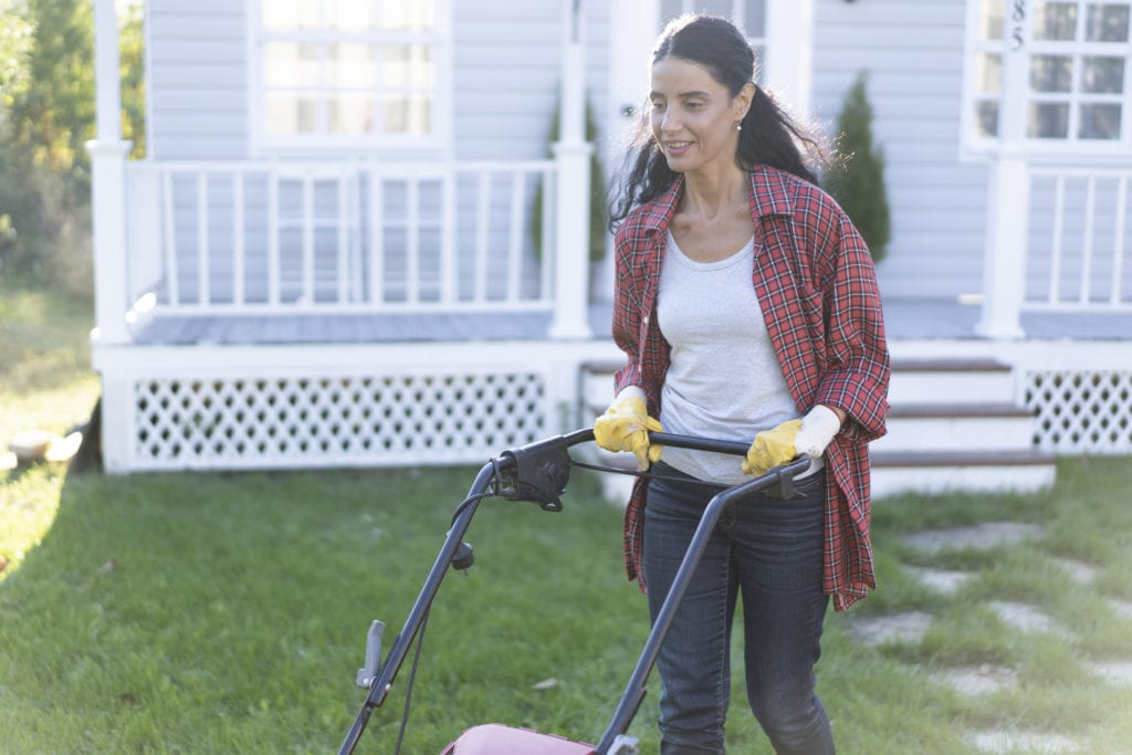 Woman mows the lawn with an electric mower, back yard.
