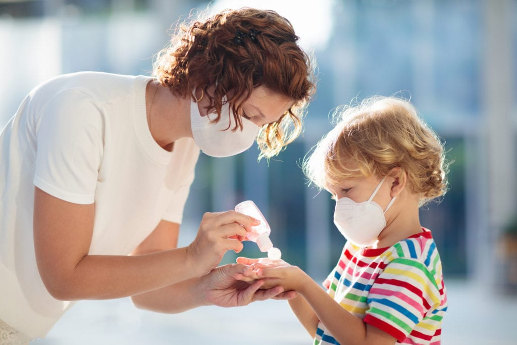 Mother and child with face mask and hand sanitizer to protect themselves while moving during the coronavirus.