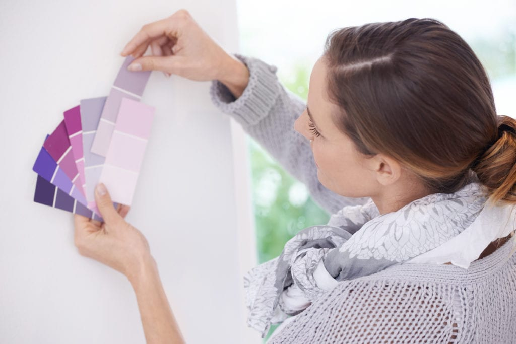 A young woman choosing the best color for her walls