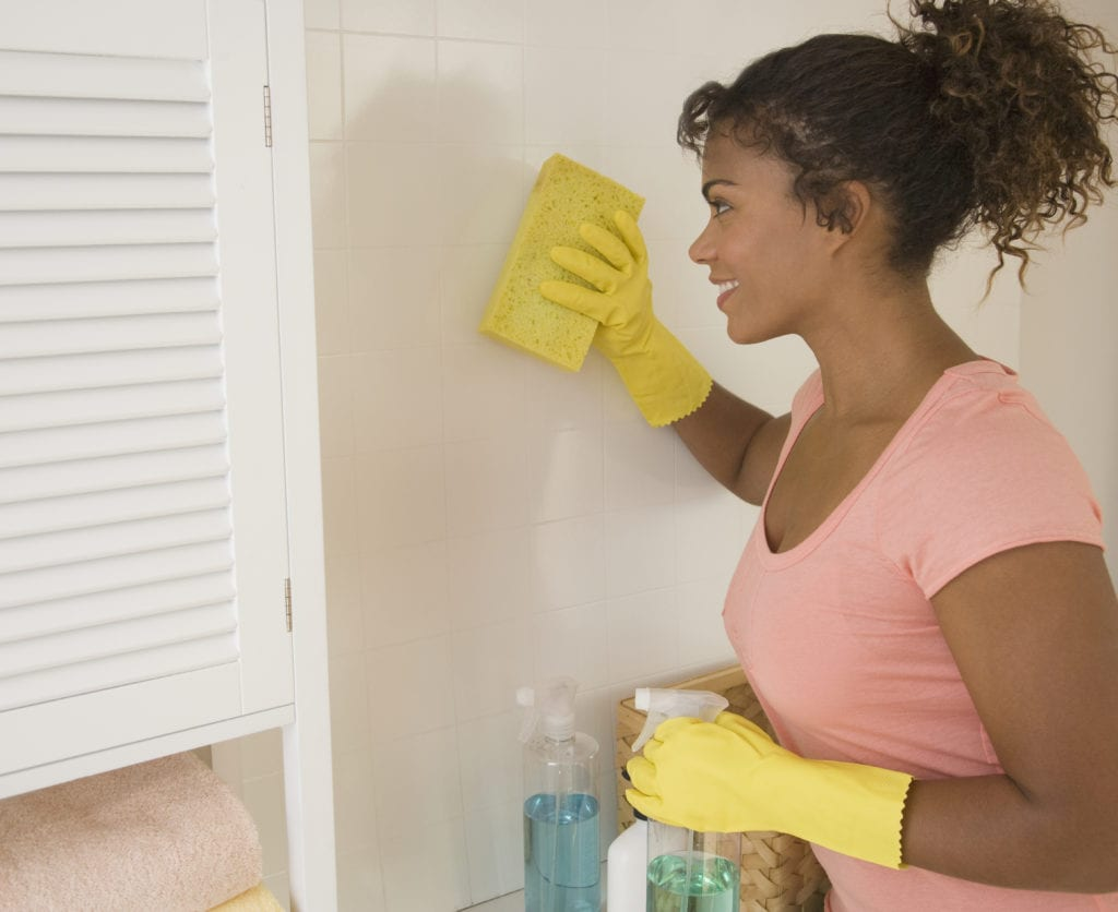 Woman removing mold from bathroom tile.