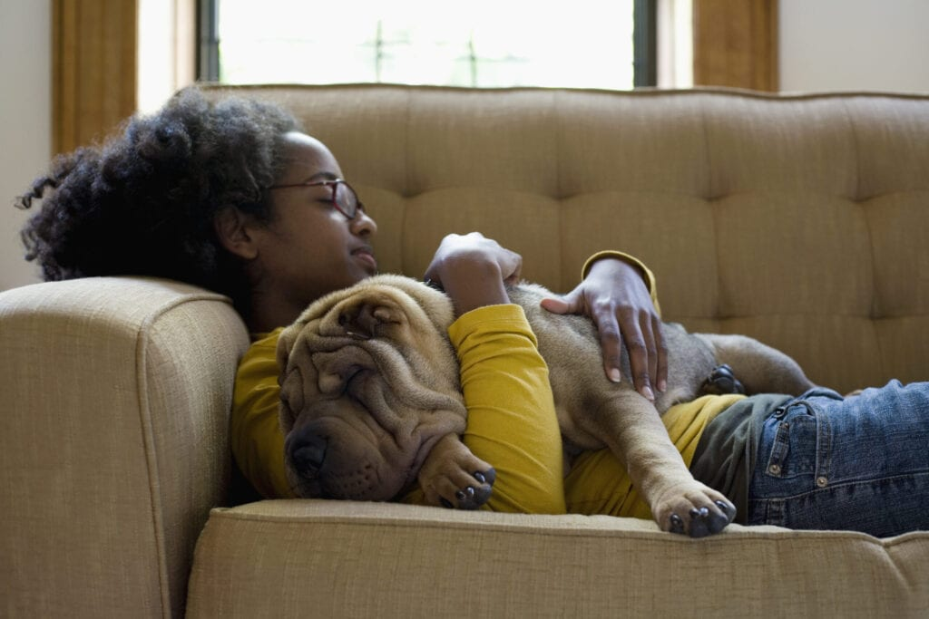 african american woman on couch with dog