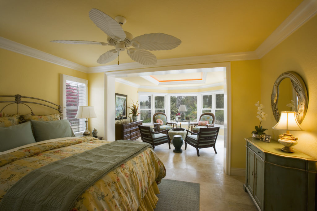 Large yellow master bedroom with sunroom