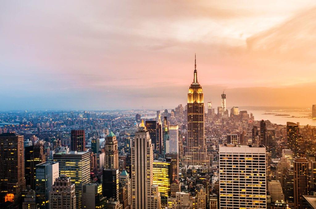 New York City skyline against colorful sunset sky