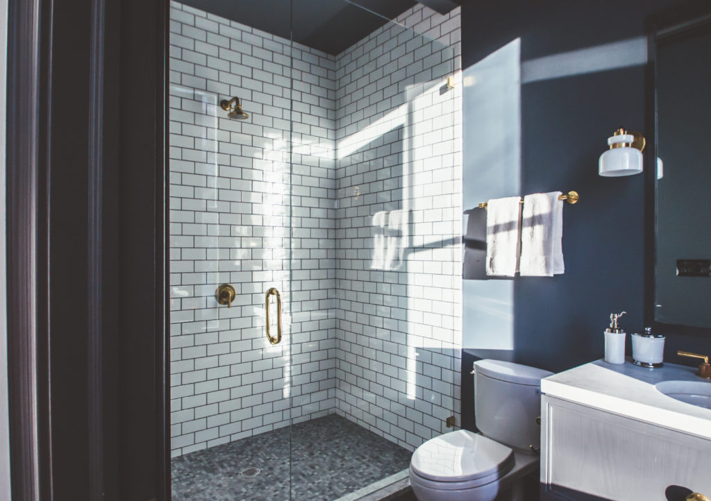 Home bathroom with dark blue walls and white subway tile shower