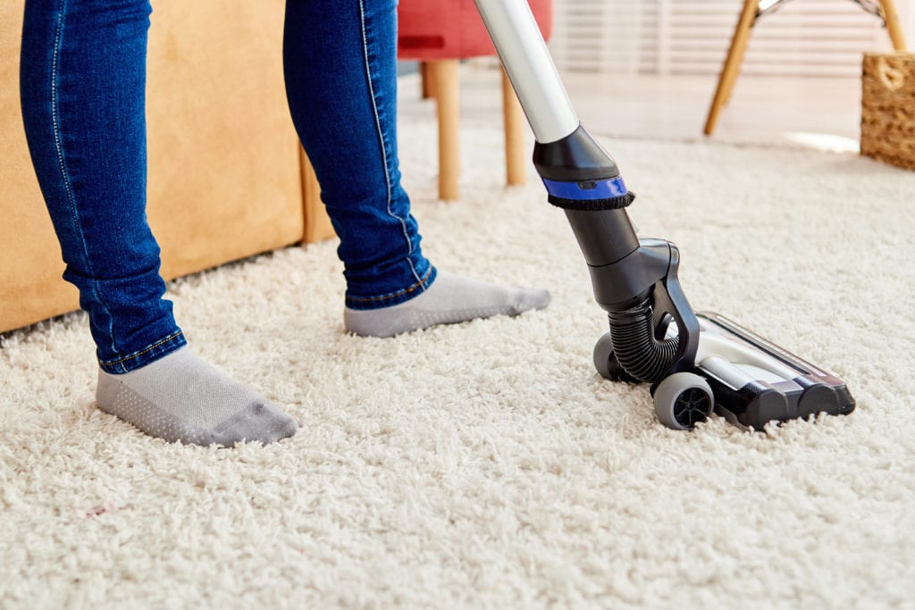 Woman vacuuming carpet in living room