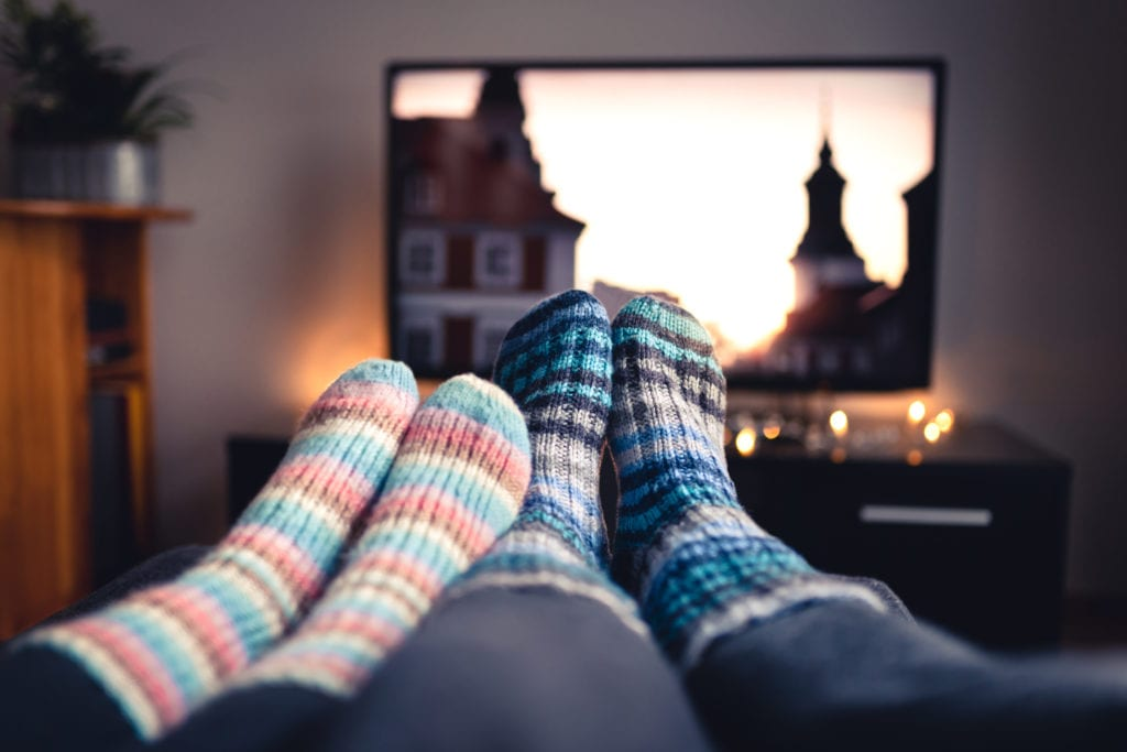 Two people watching tv at home and wearing cozy striped socks