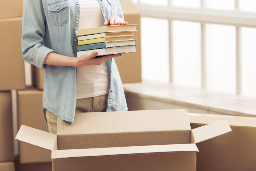 College woman packing box with books
