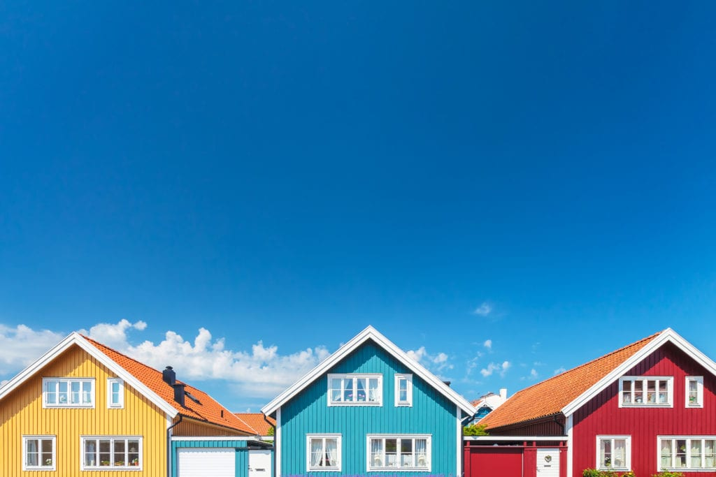 Yellow, blue, and red houses in front of a blue sky
