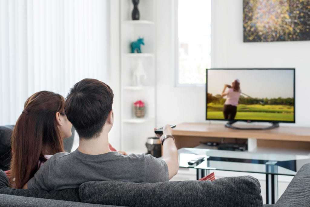 Couple watching golf on tv in their homeliving room