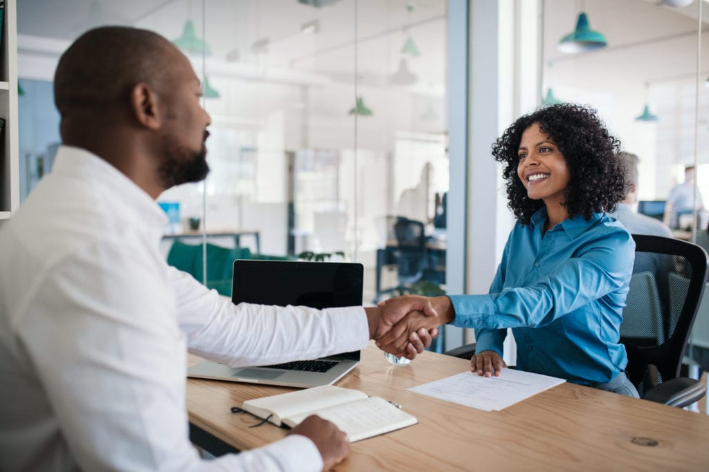 man and woman shaking hands at work