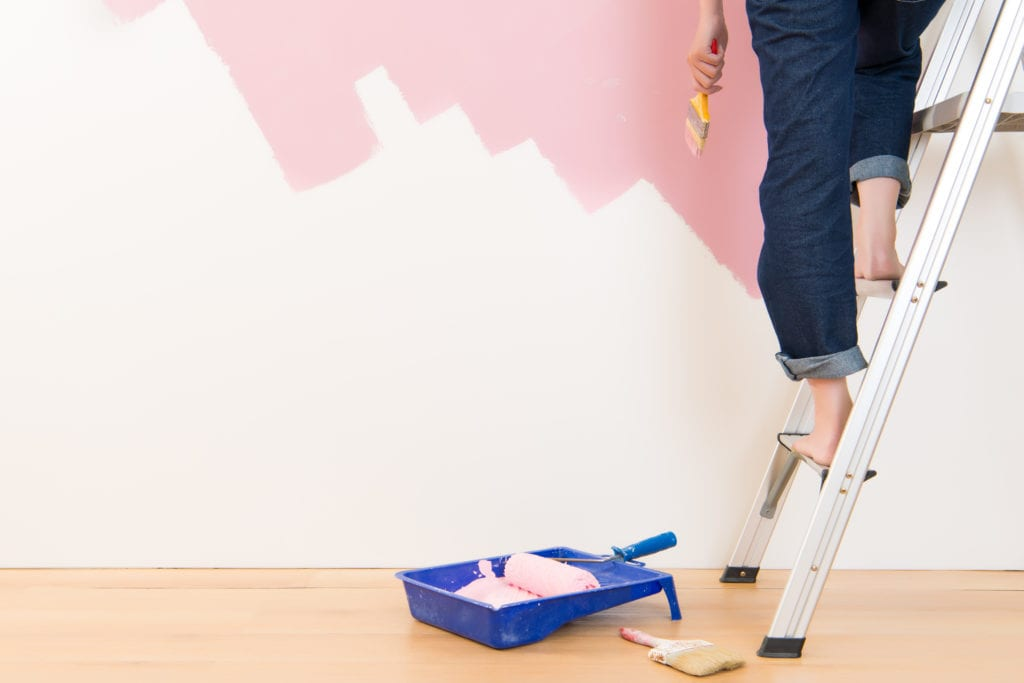 Woman standing on a ladder painting a room pink