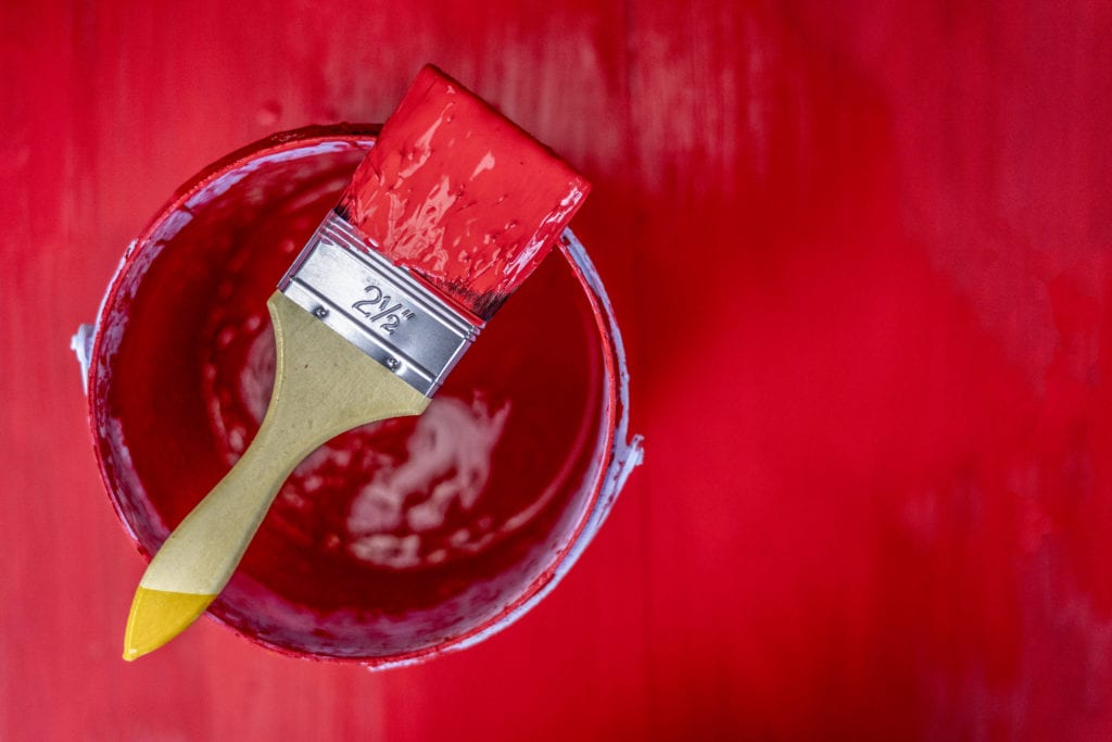 red paint can with brush on wooden plank background