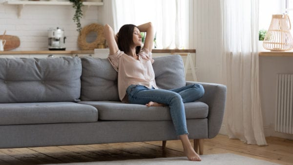 Woman relaxing comfortably in clean, modern home