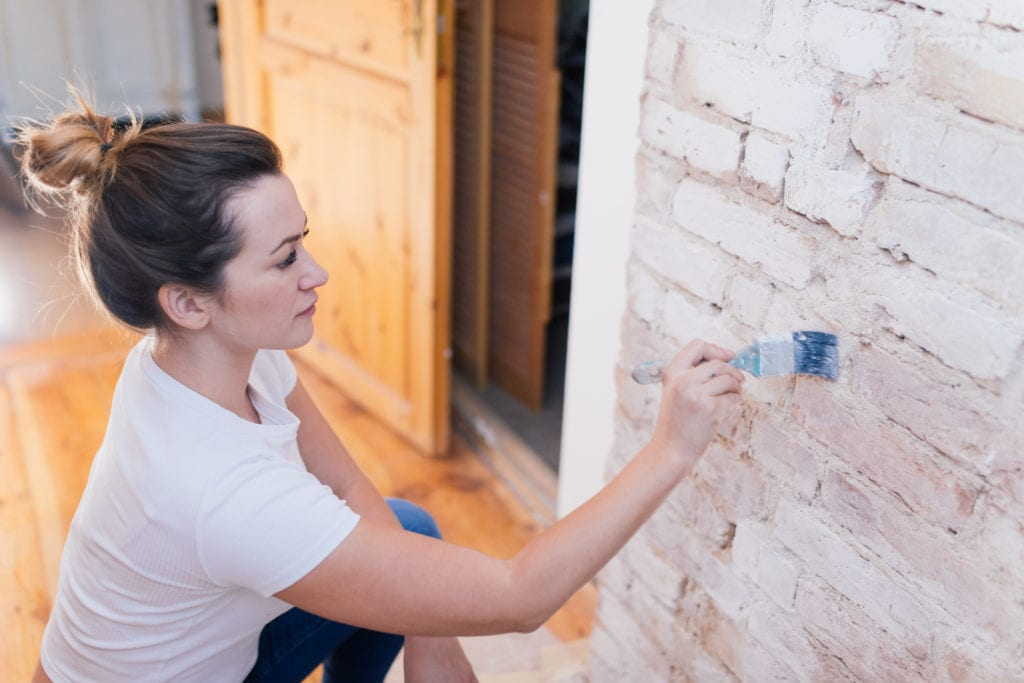 Woman painting a brick wall with milk of lime.