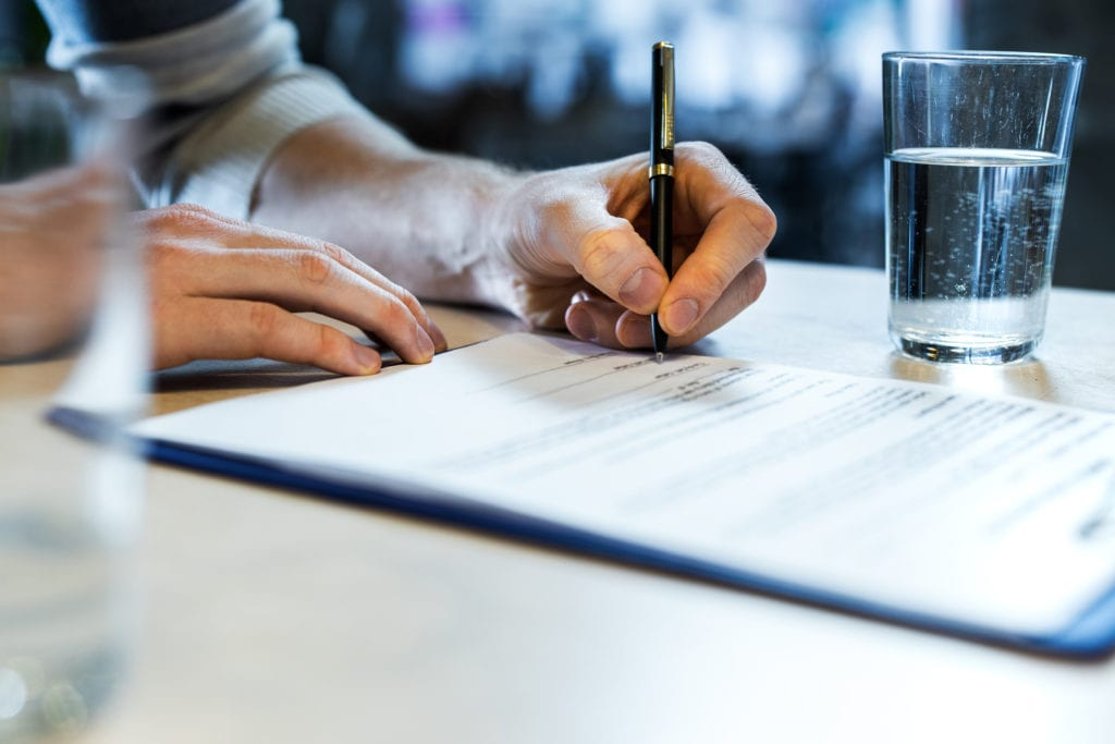 A man signing a new lease agreement. Follow these steps if your lease is set to expire during the coronavirus pandemic.