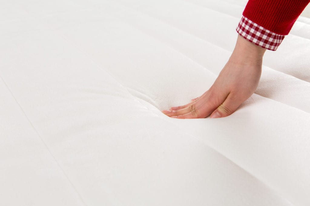 Hand pushing down on memory foam mattress