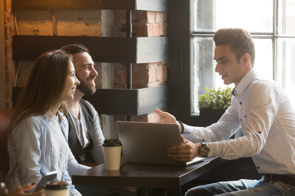 Couple talking to a mortgage broker over coffee
