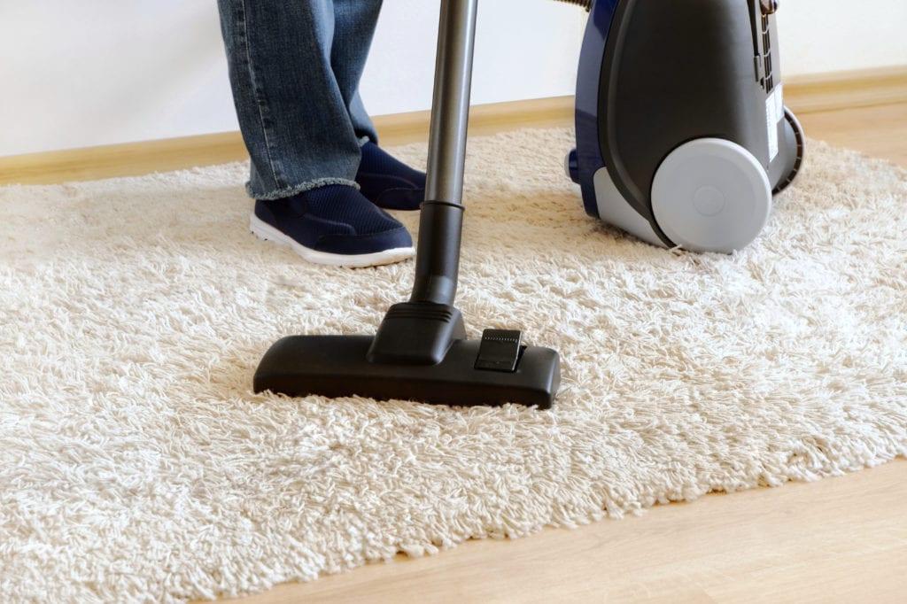 Vacuuming beige carpet