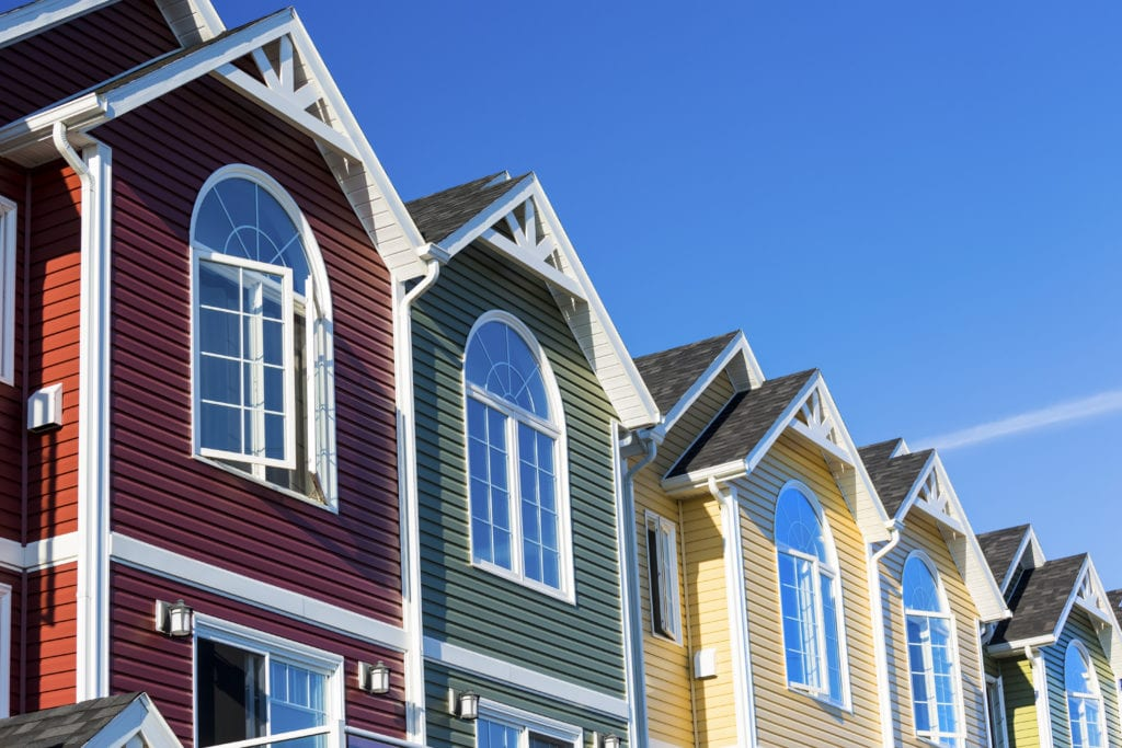 A row of colorful townhouses with vinyl siding