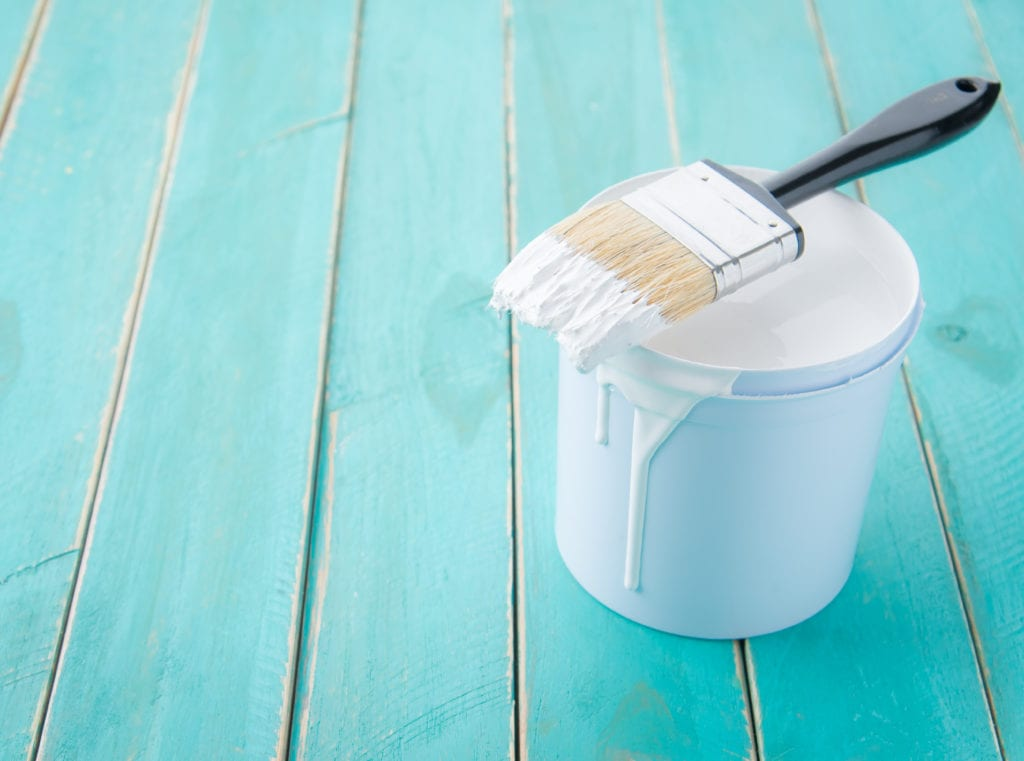 White paint against teal wooden background