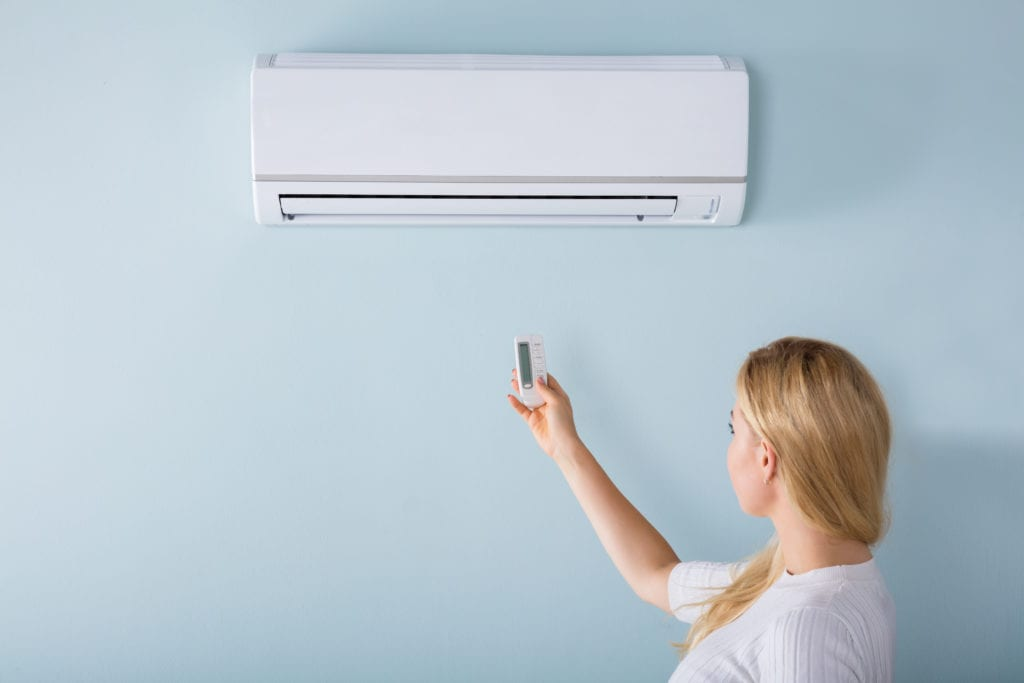 woman operating wall air conditioning unit with remote control
