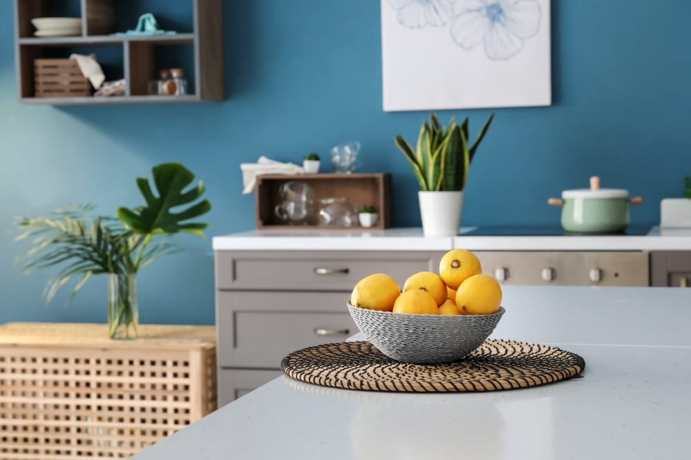 Bowl with fresh lemons on table in interior of modern kitchen