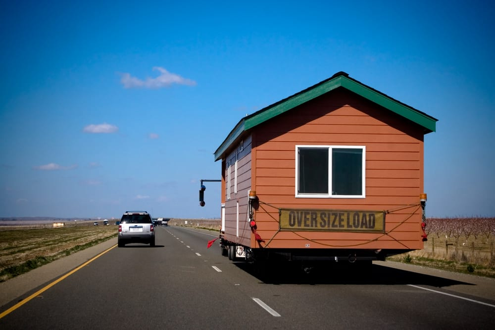 A truck moving a mobile home down the highway
