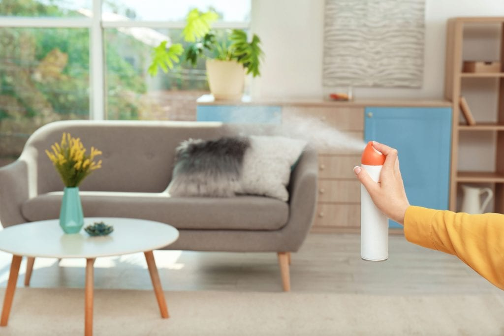 Person wearing glove sprays air freshener in living room
