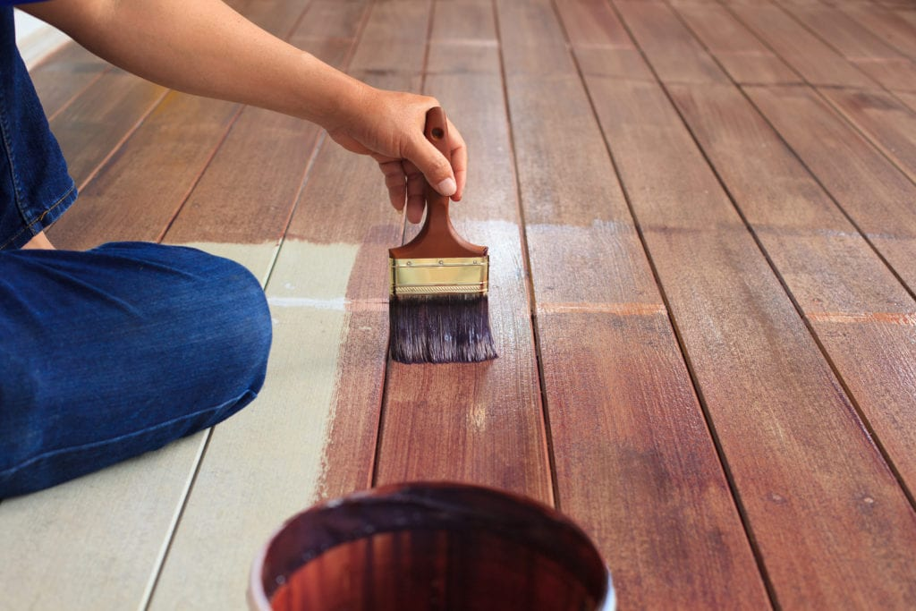 person painting outdoor deck